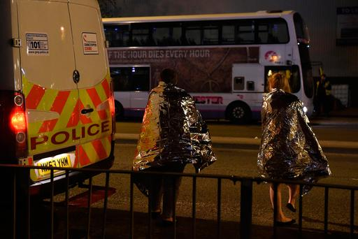 Concert goers wait to be picked up at the scene of a suspected terrorist attack during a pop concert by US star Ariana Grande in Manchester