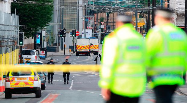 Police close to the Manchester Arena the morning after a suspected terrorist attack at the end of a concert by US star Ariana Grande left 22 dead. Peter Byrne/PA Wire
