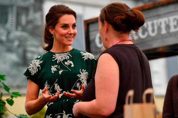Britain's Catherine, Duchess of Cambridge (L), talks to an exhibitor as she visits the Chelsea Flower Show in London on May 22, 2017
