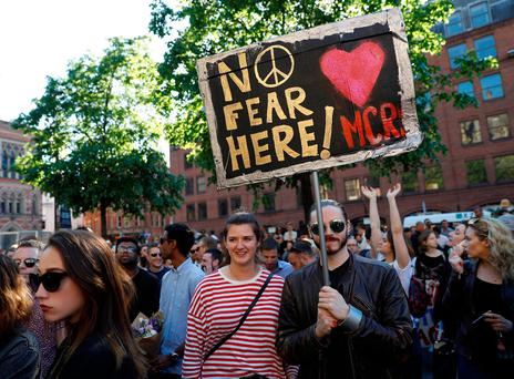 People hold a placard as they take part in a vigil for the victims of an attack on concert goers at Manchester Arena, in central Manchester, Britain May 23, 2017. REUTERS/Peter Nicholls