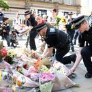 Flowers are left in St Ann's Square, Manchester, the day after a suicide bomber killed 22 people, including children, as an explosion tore through fans leaving a pop concert in Manchester. Photo: Martin Rickett/PA Wire