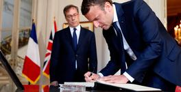 French President Emmanuel Macron signs the book of condolences at the British Embassy in Paris. Photo: REUTERS