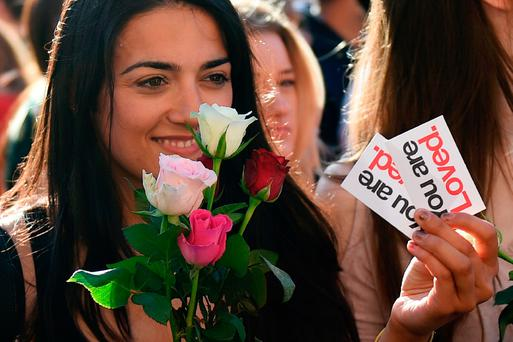 A woman hands out flowers during a vigil in Albert Square in Manchester, last night. Photo: AFP/Getty Images