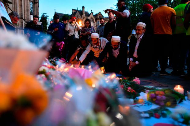 People light candles set up in front of floral tributes in Albert Square in Manchester. Photo: AFP/Getty Images
