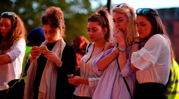 People pause in front of candles set up in front of floral tributes in Albert Square in Manchester. Photo: AFP/Getty Images