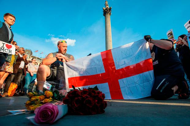The England flag is held up as people hold a minutes silence during a vigil for the victims of yesterday's Manchester Arena terror attack in Trafalgar Square in London. Photo: GETTY
