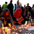 Women light candles following a vigil in central Manchester. REUTERS/Peter Nicholls