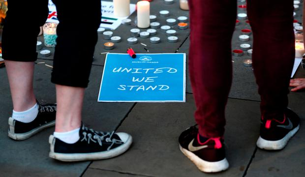 Well-wishers pay their respects to all those affected by the bomb attack, following a vigil in central Manchester. REUTERS/Peter Nicholls