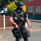 An armed police officer stands guard outside Abedi's home