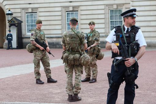 Soldiers join police officers outside Buckingham Palace, London, as armed troops have been deployed to guard