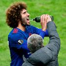 Manchester United manager Jose Mourinho helps Marouane Fellaini squeeze the water bottle. Pic: Reuters / Phil Noble Livepic