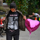 Thirteen-year-old Iqra Saied, who attended the Ariana Grande concert, looks at floral tributes and messages in Manchester yesterday. Picture: Getty
