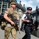 Main: Armed police and troops patrol the streets of London; inset: Suicide bomber Salman Abedi