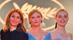 (From L) US director Sofia Coppola, US actress Kirsten Dunst and US actress Elle Fanning pose as they leave on May 24, 2017 following the screening of the film 'The Beguiled' at the 70th edition of the Cannes Film Festival in Cannes, southern France. / AFP PHOTO / LOIC VENANCELOIC VENANCE/AFP/Getty Images