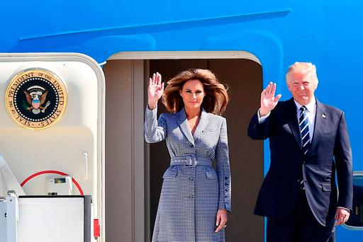US President Donald Trump (R) and First Lady Melania Trump wave as they step off the Air Force One upon arrival at Melsbroek military airport in Steenokkerzeel on May 24, 2017