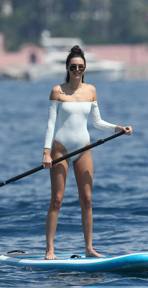 Kendall Jenner going paddle boarding in a white swimsuit Cannes on 24 May 2017 Photo credit: KCS Presse / MEGA TheMegaAgency.com