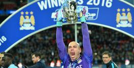 Manchester CIty's Argentinian goalkeeper Willy Caballero (C) holds up the League Cup during the presentation after Manchester City won the penalty shoot-out to win the English League Cup final football match between Liverpool and Manchester City at Wembley Stadium in London on February 28, 2016. (AFP / GLYN KIRK/AFP/Getty Images)