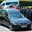 Gardai and members of the 'Sloggers to Joggers' group form a gaurad of honour as the hearse leaves after the funeral of Sandra O'Brien at St Finian's Church in Swords, Dublin. Picture credit; Damien Eagers 25/5/2017