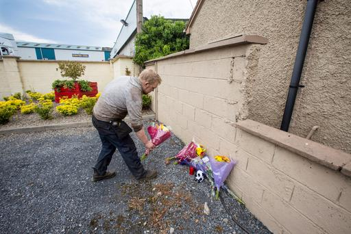A member of O'Dwyer Steel in Dundrum, County Tipperary staff lays flowers (Picture: Mark Condren)