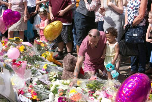 People lay tributes to the victims of the attack on the Manchester Arena in central Manchester. Photo: Kyran O'Brien