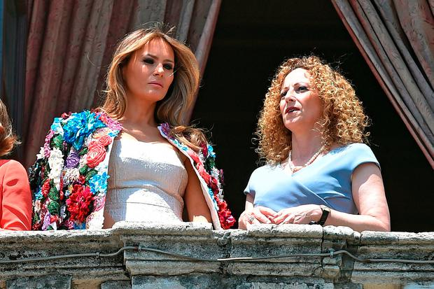 From left : US First Lady Melania Trump (L) listens to Amanda Succi, wife of Catania's mayor, Enzo Bianco, as they stand at the balcony during a visit at the City Hall of Catania on the sidelines of a G7 summit of the Heads of State and of Government in Taormina, on May 26, 2017 in Sicily