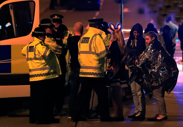 Emergency services personnel speak to people outside Manchester Arena. Photo: PA