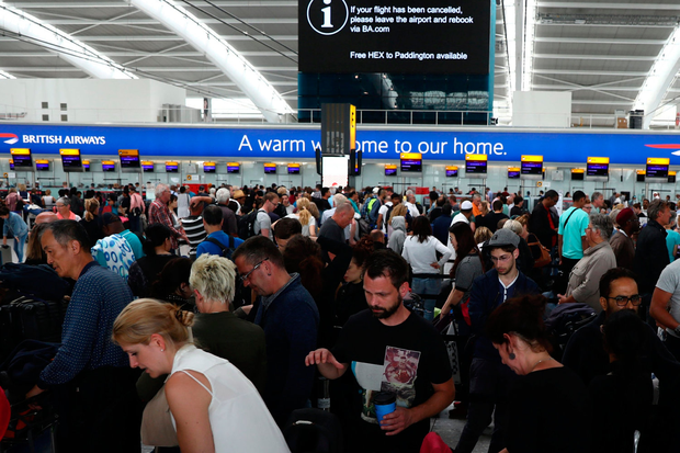 People wait with their luggage at the British Airways check in desks at Heathrow Terminal 5 in London. REUTERS/Neil Hall