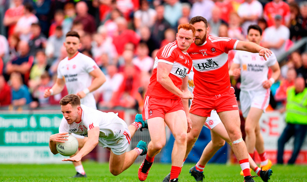 Niall Sludden of Tyrone is tackled by Conor McAtamney of Derry