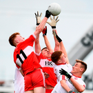 Derry's Declan Cassidy and Oisin McWilliams compete with Tyrone's Peadar Mullan, Brian McNulty and Daniel Millar for a high ball. Photo: Ramsey Cardy/Sportsfile