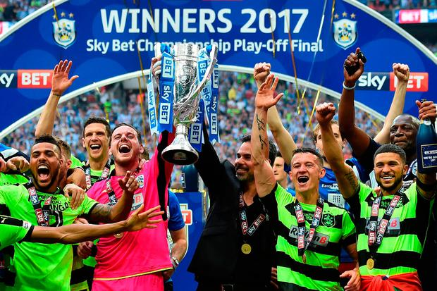 Huddersfield Town's goalkeeper Danny Ward and head coach David Wagner hold up the Championship Playoff trophy as Huddersfield's players celebrate winning the penalty shoot-out at Wembley Stadium. Pic: Getty Images