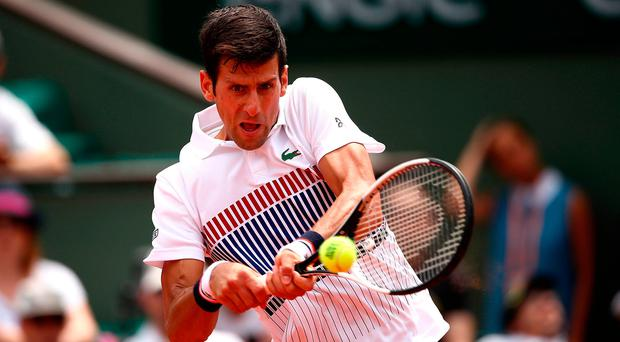 Novak Djokovic returns fire during his first round match a Roland Garros. Photo: Getty Images