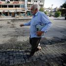 An Iraqi man walks past the site of a car bomb exploded near a cafe in Baghdad. May 30, 2017. Photo: REUTERS/Khalid al-Mousily