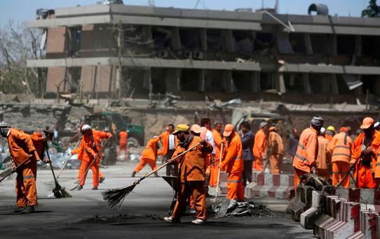 Afghan Municipality workers sweep a road in front of the German Embassy after a suicide attack in Kabul, Afghanistan, Wednesday, May 31, 2017. (AP Photos/Rahmat Gul)