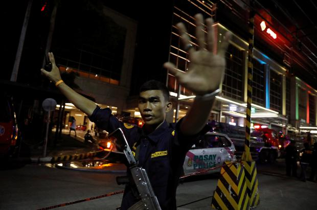A security guard stops photographers from entering the vicinity of Resorts World Manila after gunshots and explosions were heard in Pasay City, Metro Manila, Philippines June 2, 2017. REUTERS/Erik De Castro