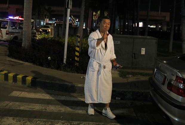 A tourist wearing a bathrobe gestures after he was evacuated from the Resorts World Manila after gunshots and explosions were heard
