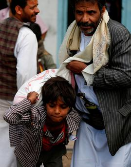 A man helps his son carry a sack of wheat flour they received from a local charity in the city of Sanaa, Yemen. Photo: REUTERS/Khaled Abdullah
