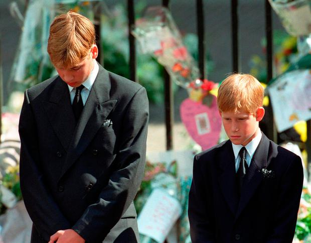 File photo dated 6/9/1997 of Prince William (left) and Prince Harry, the sons of Diana, Princess of Wales, bow their heads as their mother's coffin is taken out of Westminster Abbey following her funeral service