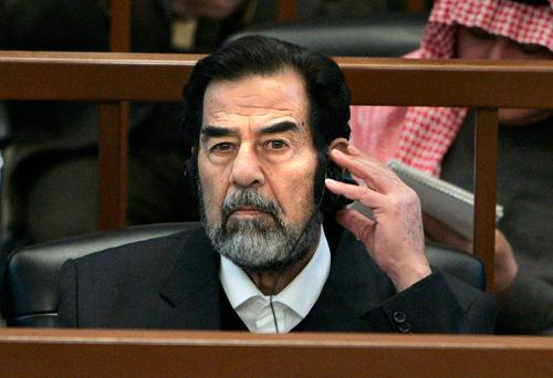 Saddam Hussein listens during his trial in Baghdad. Photo: Reuters