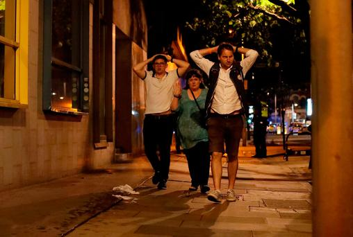 People with their hands on their heads about 10 minutes after midnight as they leave from inside a police cordon after an attack in London, Sunday, June 4, 2017. Armed British police rushed to London Bridge late Saturday after reports of a vehicle running down pedestrians and people being stabbed nearby.(AP Photo/Matt Dunham)