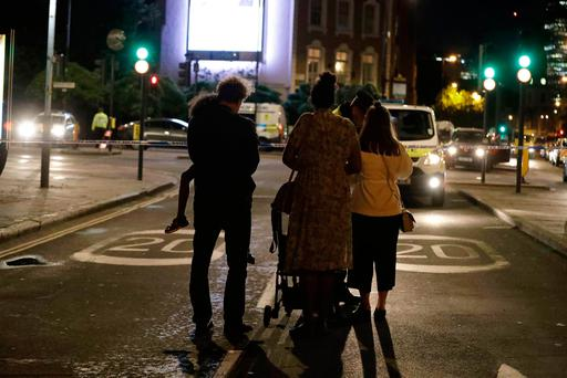 People wait by a cordon before being escorted through by police, as many residents are not allowed back to their residences inside the cordon after an attack, in London Sunday, June 4, 2017. (AP Photo/Matt Dunham)