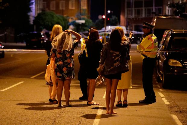 People talk to police officers at a cordon as they tried to find their way back to where they were staying after an attack in London, Sunday, June 4, 2017. . (AP Photo/Matt Dunham)