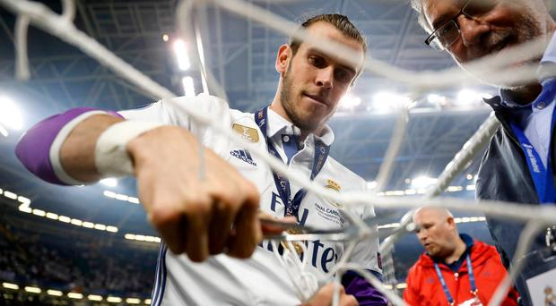 Real Madrid's Gareth Bale cuts a part of the netting from the goal after winning the UEFA Champions League Final. Reuters / Carl Recine Livepic