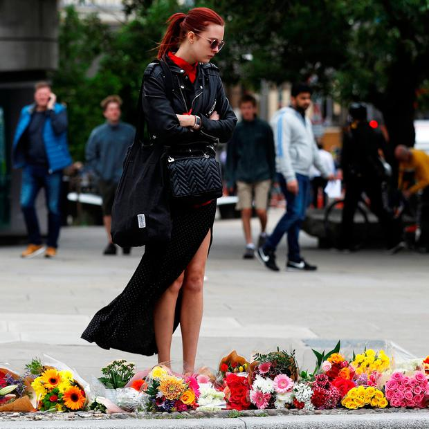 A woman looks at flowers left at the south end of London Bridge, near Borough market following an attack which left 7 people dead and dozens of injured in central London, Britain. REUTERS/Peter Nicholls