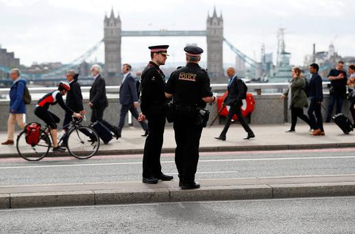 Commuters travel past City of London police officers standing on London Bridge after is was reopened following an attack which left 7 people dead and dozens of injured in central London, Britain. REUTERS/Peter Nicholls