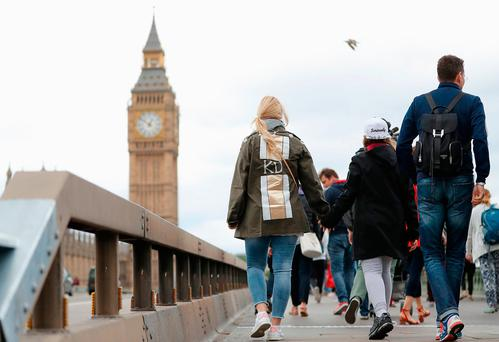 People make their way past barriers on Westminster Bridge in London which have been placed there overnight following Saturday's terrorist attack (PA)