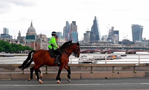 Police on horses ride past a security barrier between the road and the pavement on Waterloo Bridge in London, installed in reaction to the recent terror attacks. Photo: AFP/Getty Images