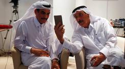 A trader uses his smartphone to stock information at Qatar Stock Exchange in Doha. Photo: Reuters