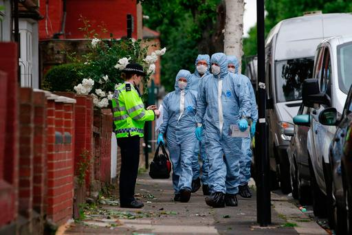 Forensics officers at a property in east London yesterday following a raid. Photo: AFP/Getty Images