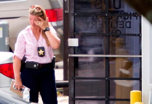 A law enforcement official wipes her eyes at the entrance to the shooting crime scene in Orlando yesterday. Photo: Reuters