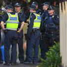 Australian police stand at the site of a siege at the Buckingham Serviced Apartments in Melbourne